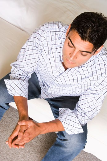 High angle view of a young man sitting with his hands clasped : Stock Photo