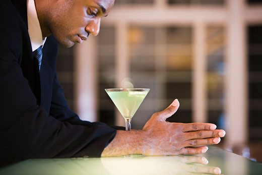 Side profile of a businessman with a glass of martini : Stock Photo