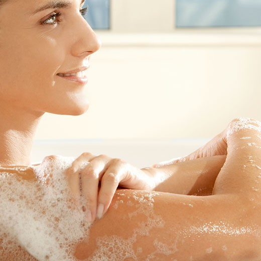 Stock Photo: 1663R-49155 Side profile of a young woman smiling in a bathtub
