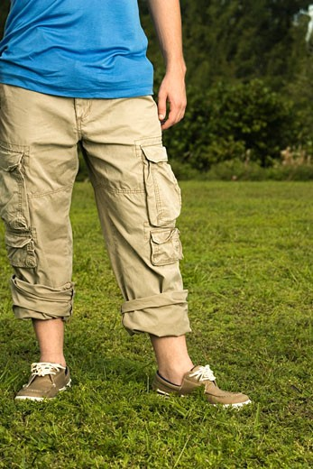 Low section view of a mid adult man standing on the grass : Stock Photo