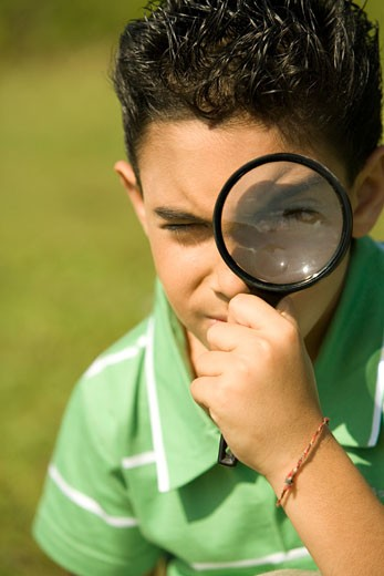 Close-up of a boy looking through a magnifying glass : Stock Photo