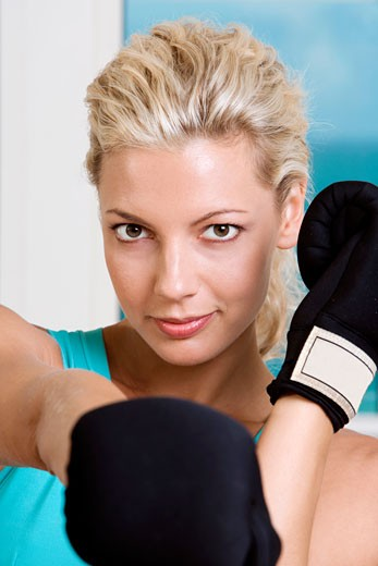 Close-up of a young woman wearing boxing gloves : Stock Photo