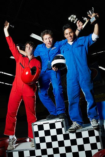 Portrait of three male go-cart racers standing on winners podium with their trophies : Stock Photo