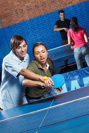 Stock Photo: 1663R-50607 Young man teaching table tennis to a young woman