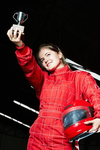 Stock Photo: 1663R-50653 Low angle view of a female go-cart racer holding a trophy and smiling