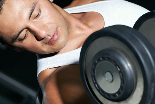 Close-up of a mid adult man exercising with a dumbbell : Stock Photo