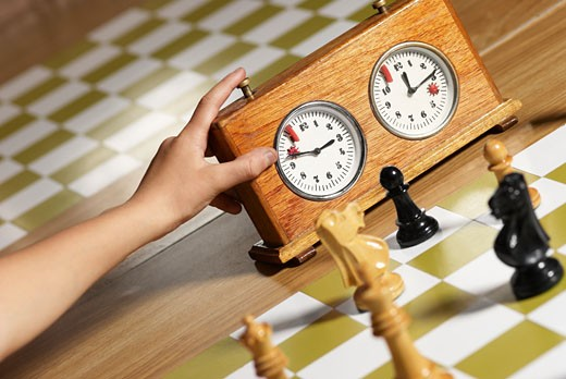 Close-up of a human hand pushing button of a chess clock : Stock Photo