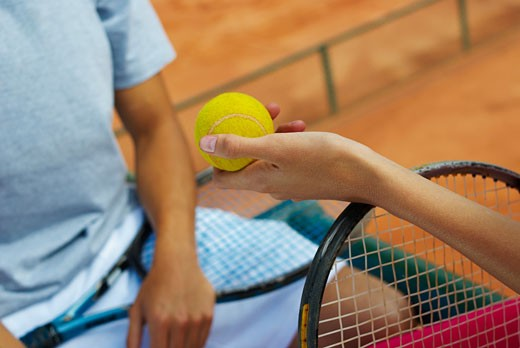 Close-up of a woman's hand giving a tennis ball to a female tennis player : Stock Photo