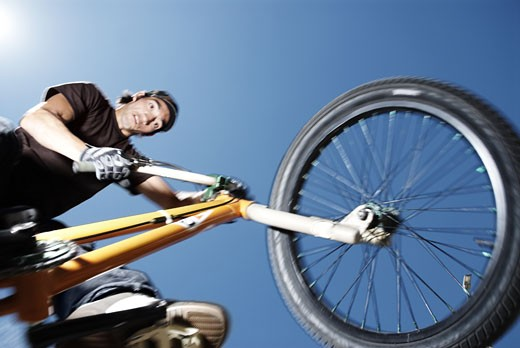 Low angle view of a young man performing a stunt on a bicycle : Stock Photo