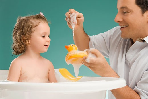 Mid adult man playing with his daughter and smiling : Stock Photo