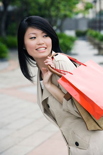 Close-up of a young woman carrying shopping bags and smiling : Stock Photo