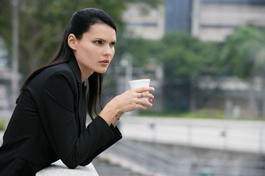 Side profile of a businesswoman holding a disposable cup and thinking : Stock Photo