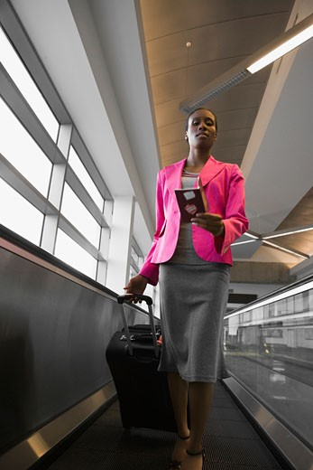 Low angle view of a businesswoman walking on an escalator at an airport : Stock Photo