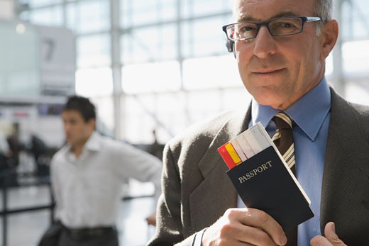 Close-up of a businessman putting a passport with an airplane ticket in his coat's pocket : Stock Photo