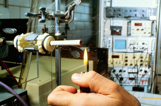 Close-up of a person's hand lighting a cigarette on a testing machine in a manufacturing plant, Richmond, Virginia, USA : Stock Photo