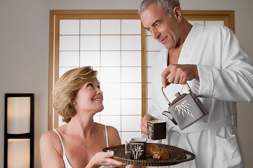Senior man pouring tea from a tea kettle into the cup with a mature woman holding a tray : Stock Photo