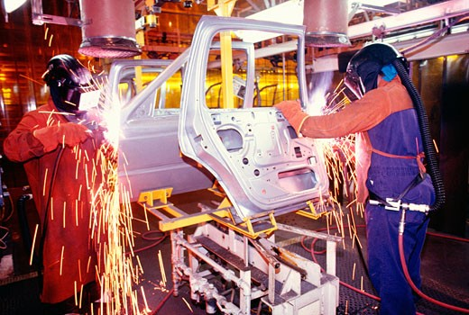Stock Photo: 1663R-5187 Welder working on car doors in an assembly line, Newark, Delaware, USA