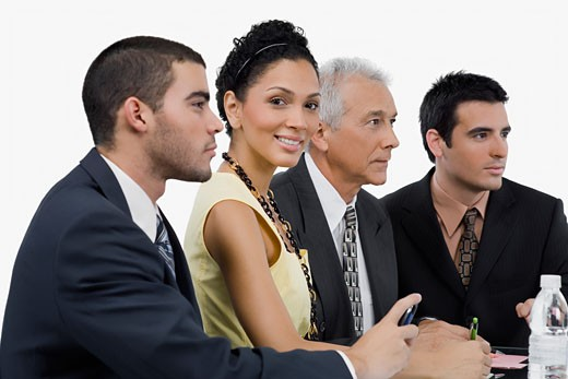 Stock Photo: 1663R-52121 Three businessmen and a businesswoman at a meeting in a conference room