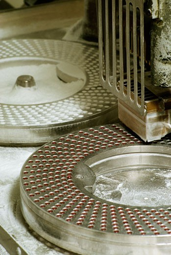 Close-up of a capsule filling machine at a pharmaceutical factory, Los Angeles, California, USA : Stock Photo
