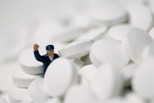 Stock Photo: 1663R-53308 Close-up of a human figurine on the heap of pills