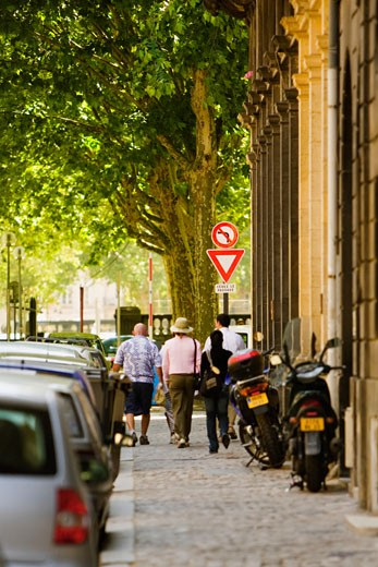 Rear view of five people walking on a sidewalk, Bordeaux, Aquitaine, France : Stock Photo