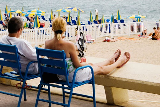 Rear view of a couple sitting in armchairs on the beach, Plage De La Croisette, Cote d'Azur, Cannes, Provence-Alpes-Cote D'Azur, France : Stock Photo