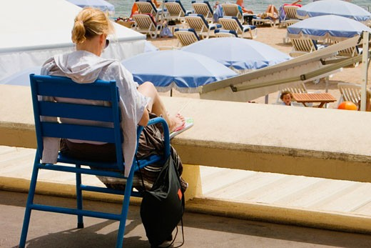 Rear view of a woman sitting in an armchair on the beach, Plage De La Croisette, Cote d'Azur, Cannes, Provence-Alpes-Cote D'Azur, France : Stock Photo