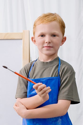 Stock Photo: 1663R-55025 Portrait of a schoolboy holding a paintbrush and smiling