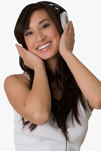 Portrait of a young woman listening to music with headphones and smiling : Stock Photo