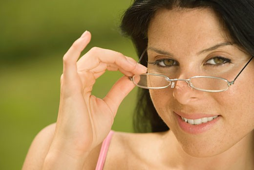 Portrait of a young woman holding her eyeglasses : Stock Photo