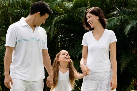 Young couple walking with their daughter in a garden and smiling : Stock Photo