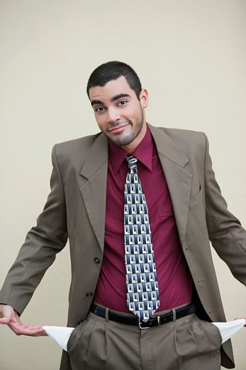 Stock Photo: 1663R-55464 Portrait of a businessman showing out his empty pockets