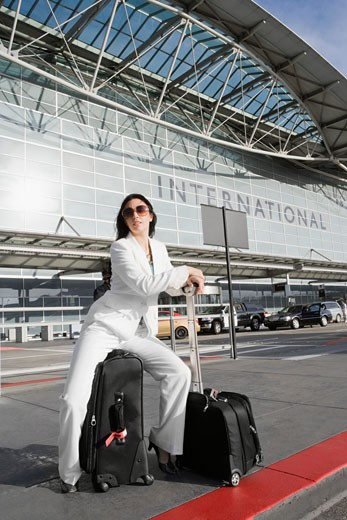 Businesswoman sitting on a suitcase and waiting for a taxi outside an airport : Stock Photo