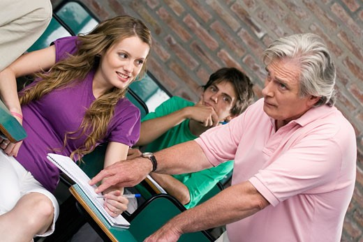 Professor assisting his students in a classroom : Stock Photo