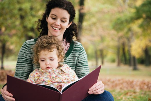 Mid adult woman and her daughter looking at a picture book : Stock Photo