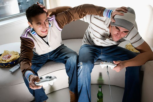 Stock Photo: 1663R-56261 High angle view of two young men playing video game and rough housing