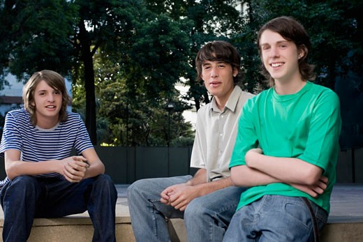 Stock Photo: 1663R-56358 Portrait of two teenage boys sitting with a young man and smiling