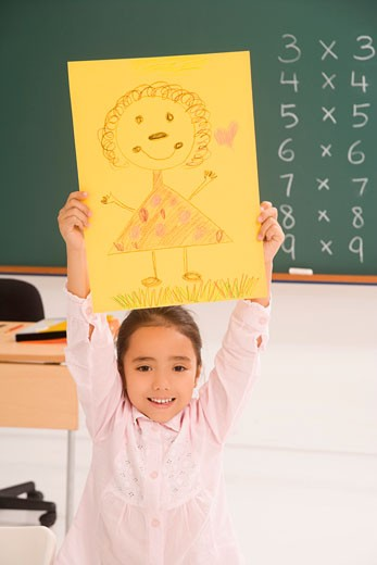 Portrait of a schoolgirl showing her drawing and smiling : Stock Photo