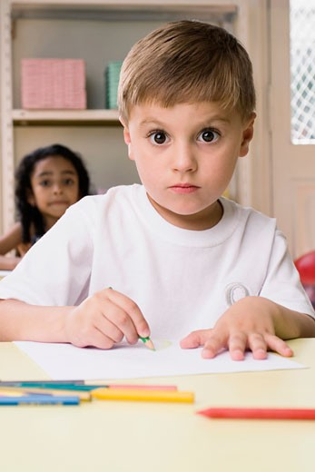 Portrait of a boy drawing on a sheet of paper with a girl sitting behind him : Stock Photo
