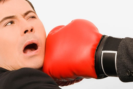 Close-up of a person's hand punching a businessman : Stock Photo