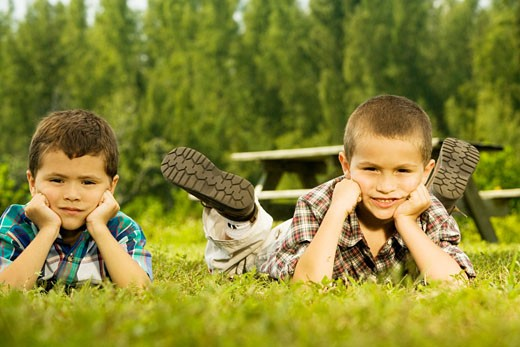 Portrait of two boys lying on the lawn : Stock Photo