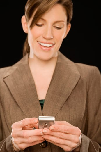 Stock Photo: 1663R-57420 Close-up of a businesswoman text messaging