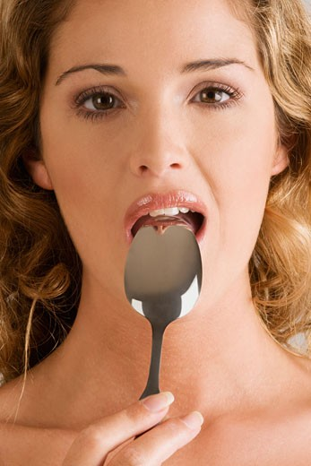 Portrait of a young woman with a spoon in her mouth : Stock Photo