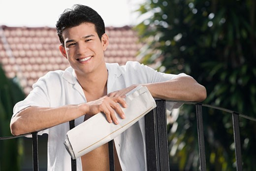 Young man holding a newspaper and smiling : Stock Photo