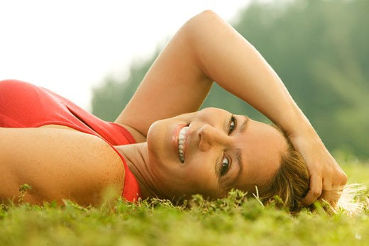Portrait of a mature woman lying on the grass : Stock Photo