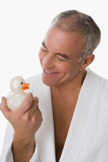Close-up of a senior man holding a toy duck and smiling : Stock Photo