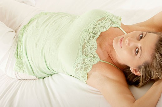 Portrait of a mid adult woman lying on the bed : Stock Photo
