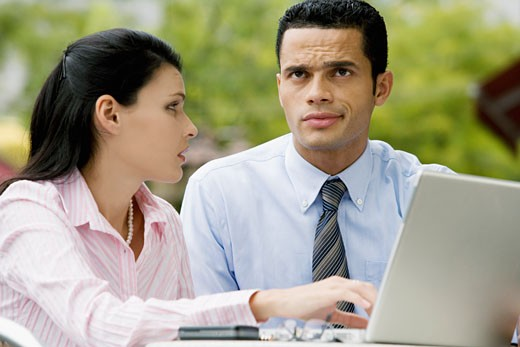 Businesswoman using a laptop with a businessman sitting beside her : Stock Photo