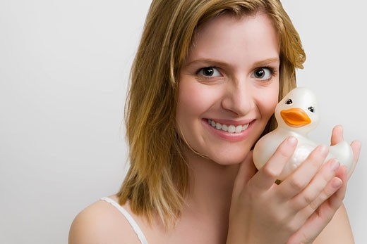Portrait of a teenage girl holding a rubber duck and smiling : Stock Photo