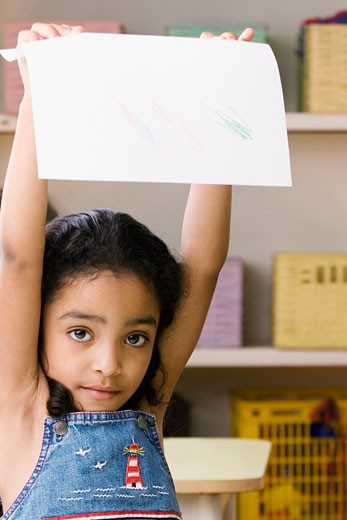 Portrait of a girl showing a drawing : Stock Photo